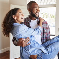 man carrying partner into new home